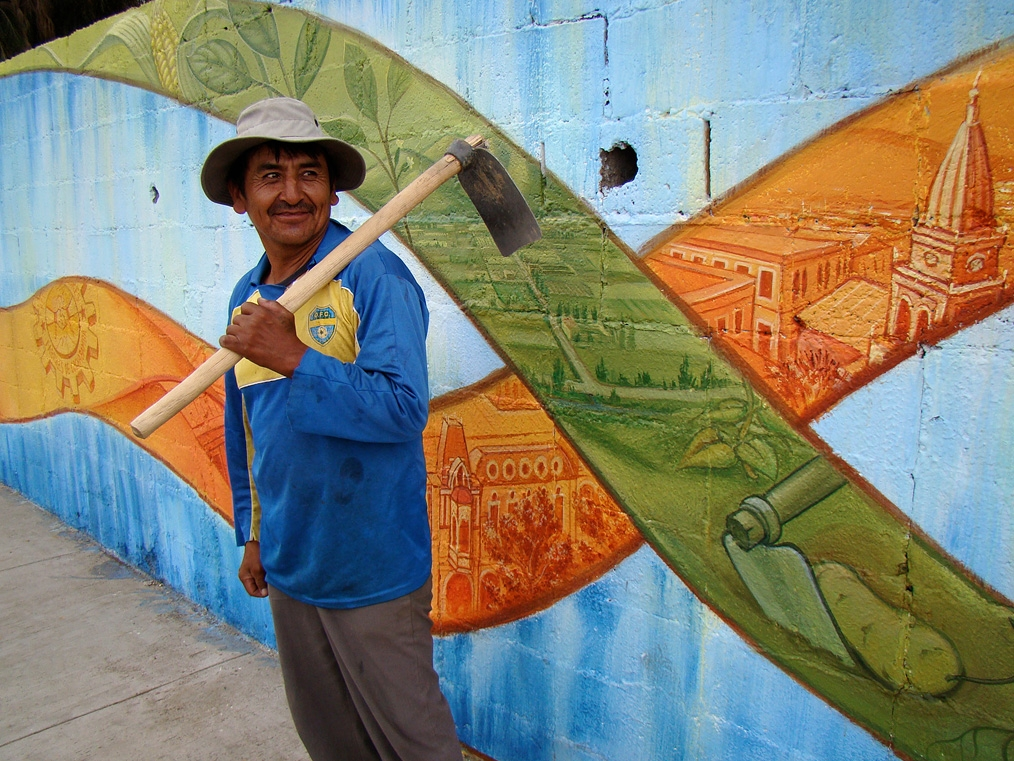 The owner of the hoe that was painted in the mural.<br />In the green ribbon: the Cochabamba plains with the irrigation canals of the regantes, the hills with subsistence farming of the campesinos, and the coca leaves going over the hills to the Chapare, where the cocaleros came from to join Cochabamba's struggle.