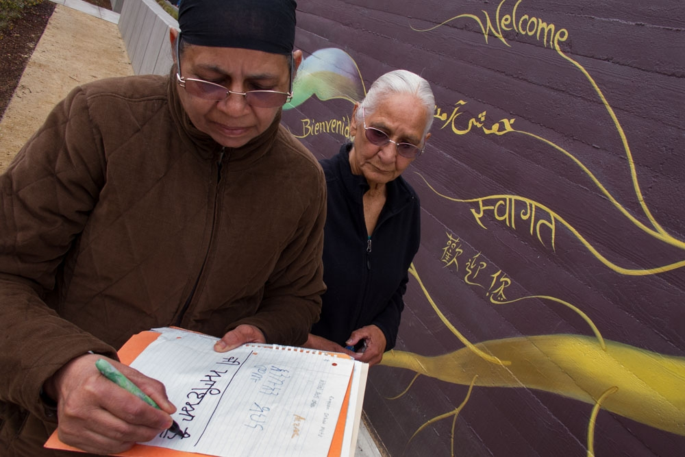 Local residents contributing words of welcome to the mural, in their native languages